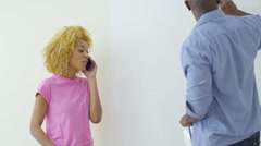 4K Happy couple in new home, woman makes a phone call while her partner paints - stock footage