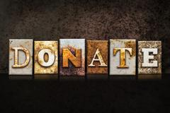 Donate Letterpress Concept on Dark Background - stock photo