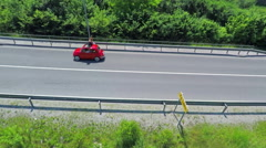 Red yugo driving overpassing a highway Stock Footage