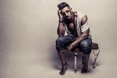 Muscular Man in Ragged Clothes Sitting on a Chair Stock Photos