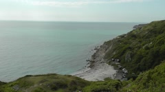 View from above onto Church Ope Cove beach and huts, Isle of Portland, UK Stock Footage