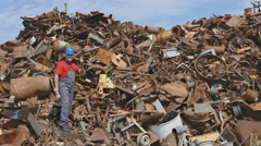 Recycling, worker at heap of metal - stock footage