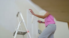4K Attractive young woman painting a wall in new home Stock Footage