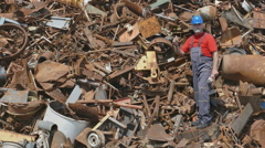 Recycling, worker at heap of metal Stock Footage