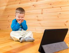 Very pleased little boy enjoying watching his tablet computer Stock Photos