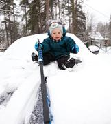 Funny baby boy cleans car bonnet from snow - stock photo