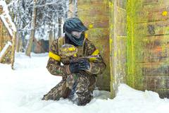 Experienced sportsman in professional paintball armor on winter training outd Stock Photos