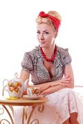 Pinup woman sitting at tea table - stock photo