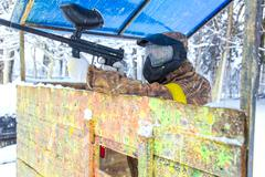 Man shooting from paintball gun behind wooden fortification Stock Photos