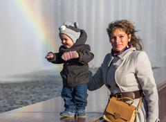 Smiling toddler with his mother standing near rainbow Stock Photos
