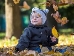 Yellow leaves falling on sitting little boy - stock photo