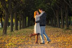 Two happy lovers on sunny alley in the park Stock Photos