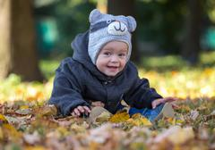 Happy baby sitting on the fallen leaves outdoors Stock Photos