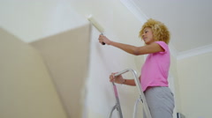 4K Attractive young woman painting a wall in new home - stock footage