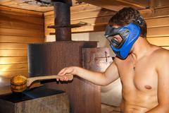 Young man sitting in sauna in paintball mask Stock Photos