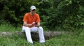 Man with smartphone sits on a fallen tree in the forest Footage