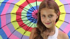 Beautiful girl with colorful umbrella looking into the camera Stock Footage