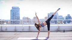 Beautiful sports girl does exercises Pilates and yoga on the roof Stock Footage