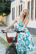 Romantic blonde girl with bicycle - stock photo