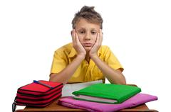 Boy with books looking bored. All on white background. - stock photo