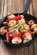 Chicken shish kebabs on a cast iron skillet - stock photo