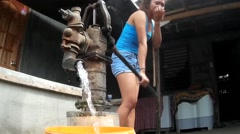 Lady pumping water from deep well - stock footage