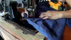 Woman sewing blue coat Stock Footage