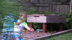 Young boy runs toward sprinkler. - stock footage