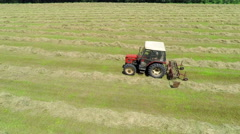 Tractor working on a field of grass Stock Footage