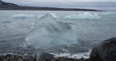 Clear Ice Berg Rests in Arctic Surf of Bay - Static Close Stock Footage
