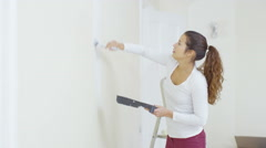 4K Happy woman painting a wall in new home turns to smile at camera - stock footage