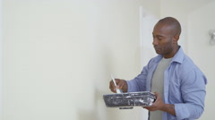 4K Happy man painting a wall in new home turns to smile at camera - stock footage
