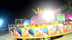 Wide shot of moving rides and enjoying youths. Stock Footage