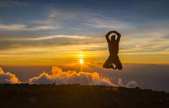 Stock Photo of Man jump through the gap on sunset fiery background. Element of design