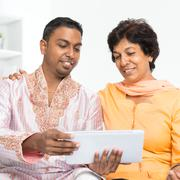 Indian family using social network - stock photo