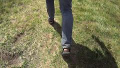Feet in sandals walking on grass Stock Footage