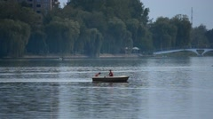 Couple rowing in a boat on a lake Stock Footage