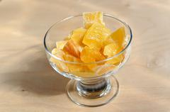 Dried sweet pieces of mango in bowl on wooden surface Stock Photos
