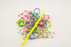 elastic rainbow loom bands on white background. - stock photo