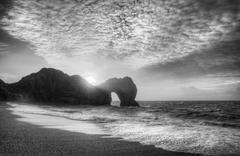 Vibrant sunrise over ocean with rock stack in foreground in black and white Stock Photos
