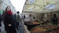 People buy baked hot food from in outdoor market tent Arkistovideo