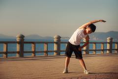 Vietnamese boy does bending aside on embankment at dawn Stock Photos