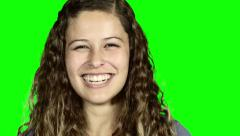 Brown-eyed young beauty on green screen turns to camera and laughs. Stock Footage