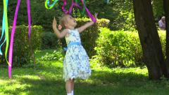 Happy girl playing with colored ribbons in the summer park and sincerely rejoice - stock footage