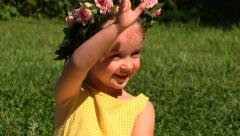 Little girl joyfully welcomed, waving hand and points in summer park. Slow mo Stock Footage