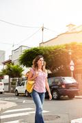 Young woman of caucasian ethnicity walking down a brightly lit street - stock photo