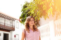 Waist up portrait of a young woman with wavy hair walking outdoors during the Stock Photos
