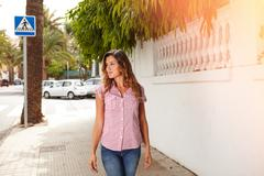 Young woman in brightly lit day smiling while walking outdoors - copy space Stock Photos