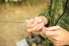 The fisherman attaches a sinker on the line Stock Photos