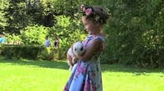 Girl in beautiful dress and a wreath gently holding the rabbit in her hands Stock Footage